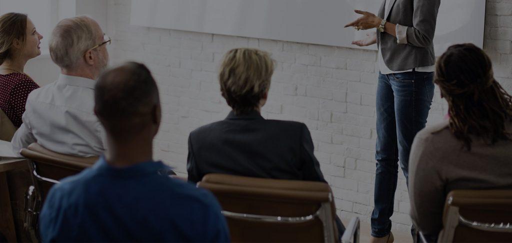 Dame qui donne un cours dans une salle remplie. Il y a exactement 6 personnes.